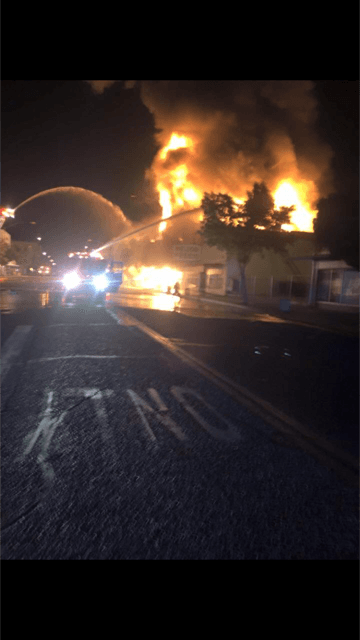 Fire Being Fought by Truck Hose at Night