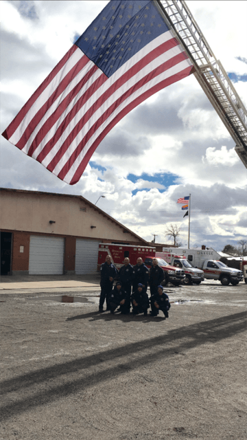 Firefighters Standing Next to American Flag and Department Building