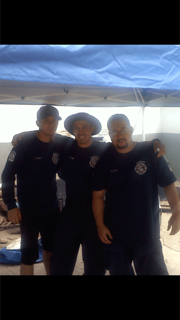 Group of Firefighters Coming Together for a Picture under a Tent