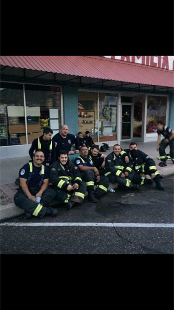 Group of Firefighters Sitting on Curb for Group Photo