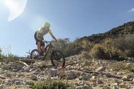 A man riding a bicycle on rocky terrain